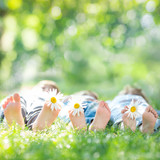 Fototapety Family with flowers lying on green grass. Healthy lifestyle conc