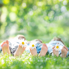 Family with flowers lying on green grass. Healthy lifestyle conc