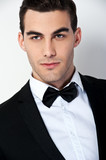 Man in black dinner jacket with bow tie. Bridegroom