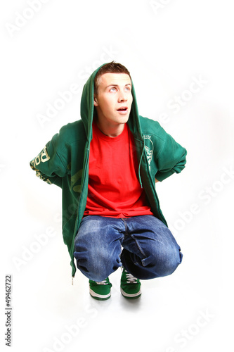Cool hip hop style dancer sitting and looking up isolated on whi
