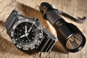 military watch and flashlight
