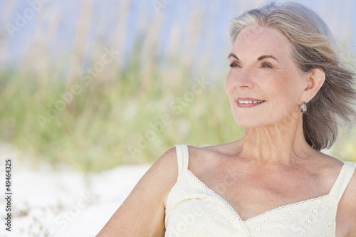 Attractive Senior Woman Sitting At Beach