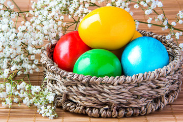 Colored painted eggs in a wattled basket with flowers