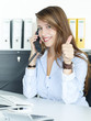 Business woman having a good call at work and shows thumb up