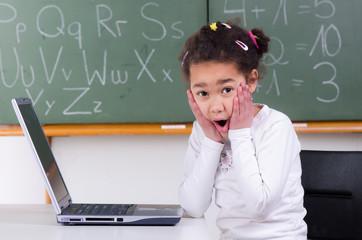 schülerin sitzt erschrocken vor laptop
