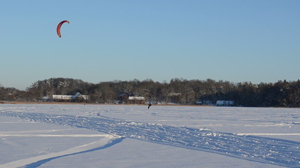 man kiteboarding with snowboards on frozen lake winter hobby