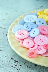 Pink and blue buttons on a light yellow plate