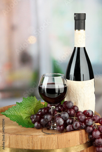 Composition of wine bottle, glass and  grape,on wooden barrel,