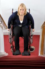 Junge Frau im Rollstuhl vor Treppe als Hindernis
