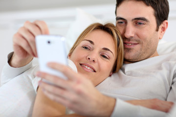 Couple laying in sofa and using spartphone