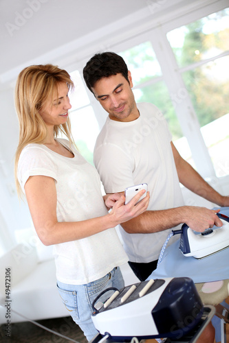 Girl bothering boyfriend while ironing shirt