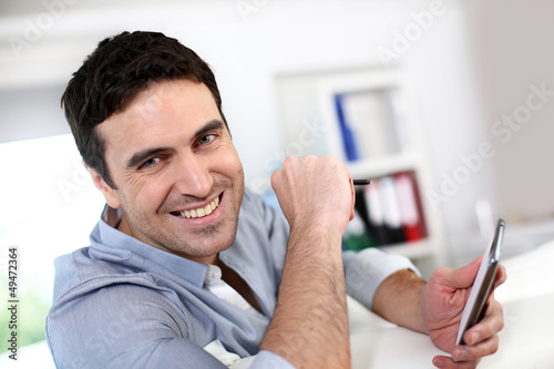 Smiling guy connected on smartphone