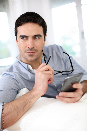 Man sitting in sofa and using smartphone