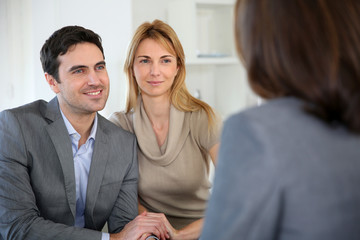 Cheerful couple receiving good news from advisor
