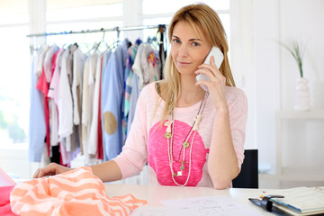 Woman designer in workshop talking on the phone