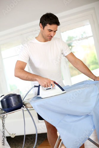 Man ironing shirt before leaving for work