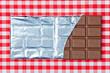 Tafel Schokolade auf kariertem Tischtuch