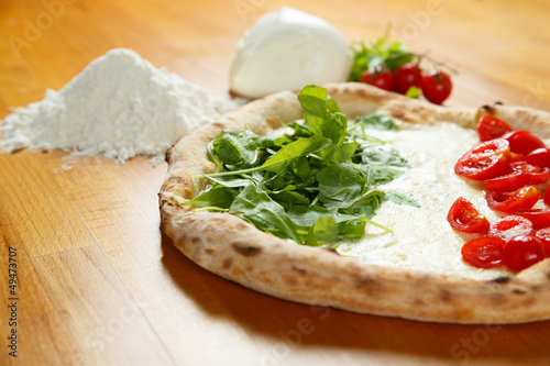Typical Italian Pizza, ingredients in background on wood table