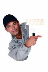 Tradesman holding a paint roller and pointing to a blank sign