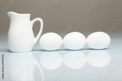 Milk in a glass jar and eggs