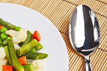 Sliced ​​vegetables on a plate and spoon