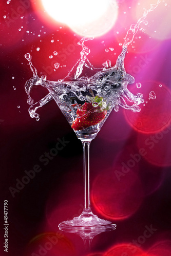 Martini with splashing strawberry