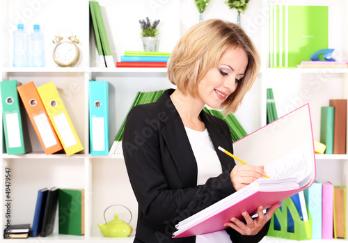 Beautiful young business woman working in office