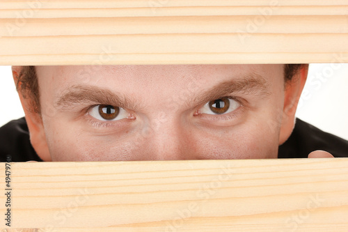 Man eyes looking through hole in wooden desk