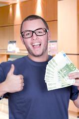 Jeune homme tenant dans la main une liasse de billets.