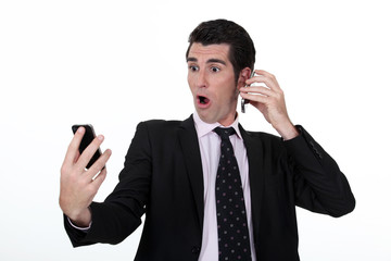 businessman holding two cell phones