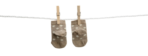 Brown baby socks hanging on clothesline isolated
