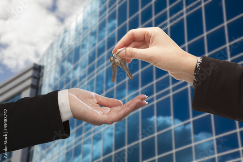 Female Handing Over the Keys in Front of Corporate Building