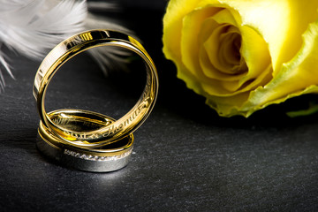 Eheringe auf Schieferplatte mit gelber Rose und Feder