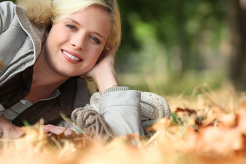 Blonde woman on a bed of dry leaves