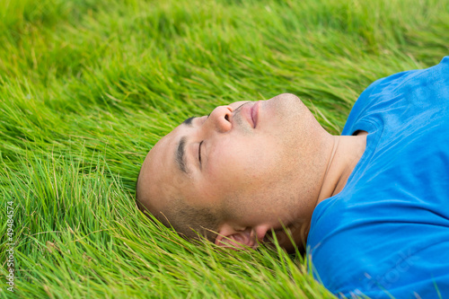Fat Man Lying on the Green Grass to Relax.