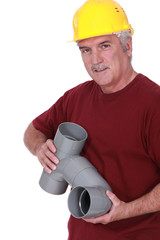A plumber holding parts