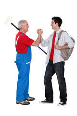 A mature painter shaking hand with his trainee.