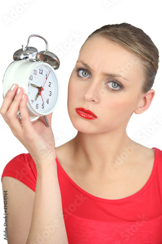 Serious looking blond woman holding alarm clock