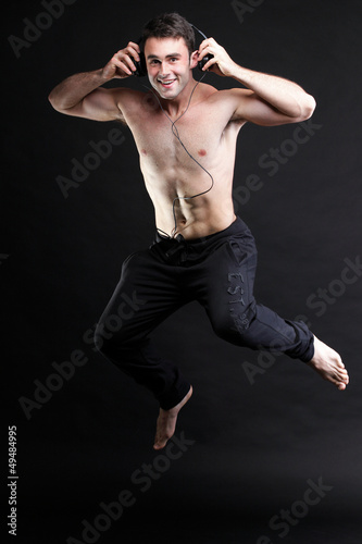 Young man jumping and listening music isolated gray background