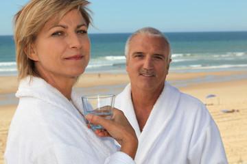 Couple on a beach in bathrobes