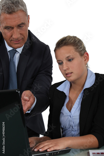 Boss and employee in front of laptop computer