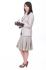 Woman in a skirt suit writing in a personal organizer
