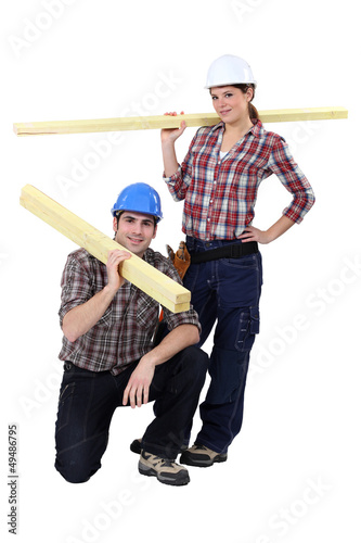 Labourers carrying wooden planks
