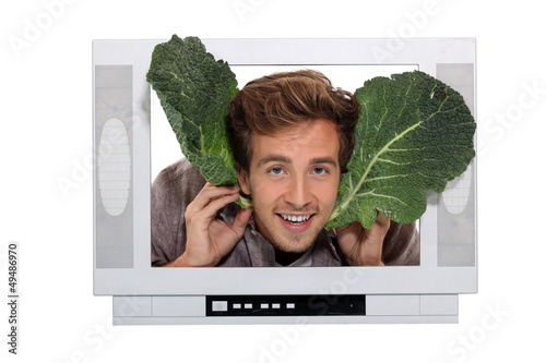 Man with cabbage leaves inside a television