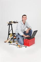 Carpenter kneeling by laptop