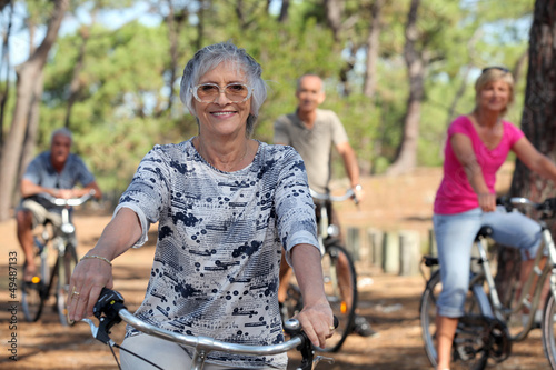 old woman and three other people doing bike in the forest