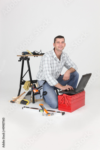 Carpenter kneeling by laptop