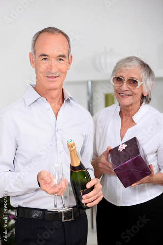 Older couple with champagne and a gift