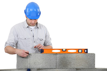 bricklayer erecting concrete wall