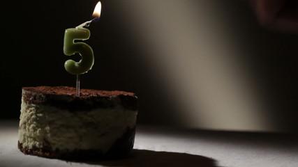 Candle five in tiramisu cake.